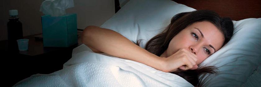 Mujer tosiendo en la cama
